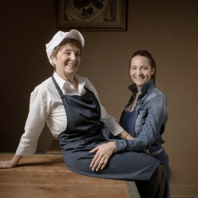 Deux femmes l'une à côté de l'autre, la première à gauche assises sur une table en tablier bleue et casquette blanche, la seconde assises à ses côtés en tablier bleu