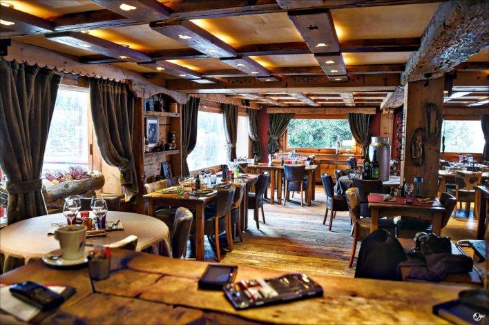 Salle de restaurant, dans un chalet typique avec poutre apparente et grandes fenêtres donnant sur la nature