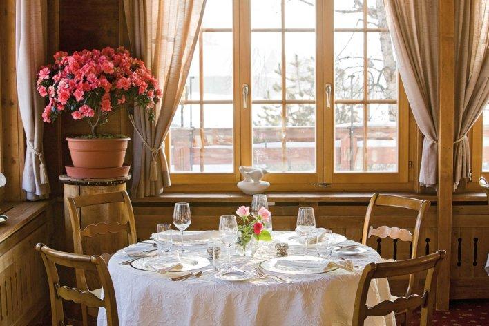 Table dressée pour quatre couvert dans une salle de restaurant de chalet tout en boiserie, nappe blanche brodée et pot de fleur sur-élevé