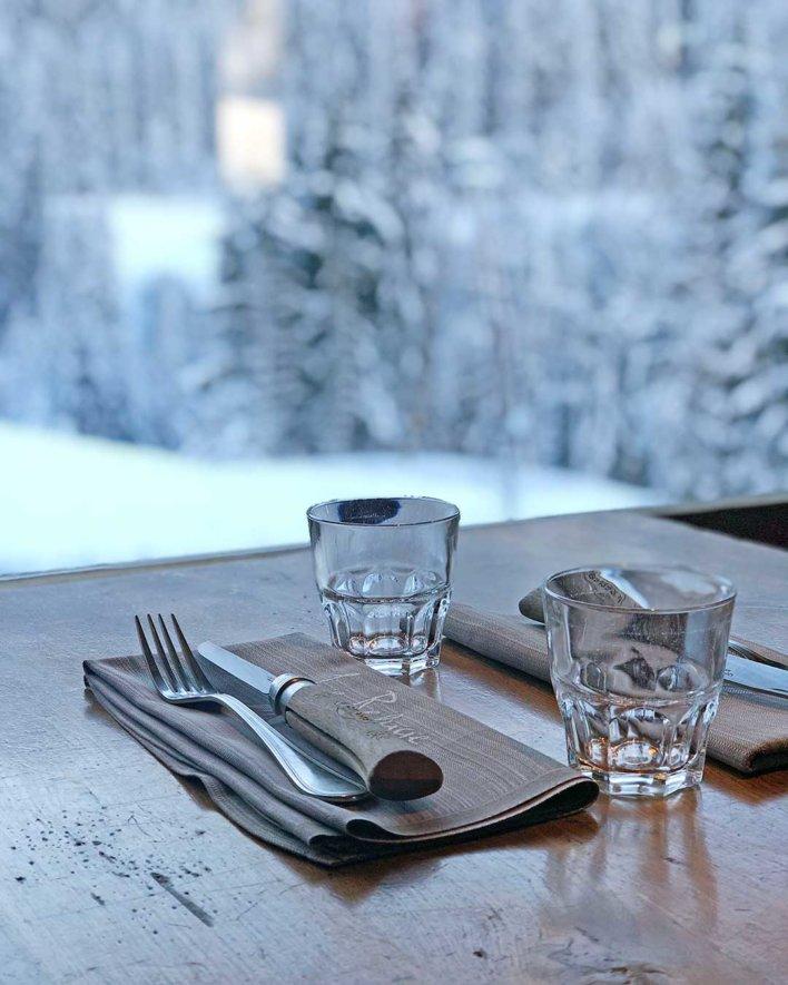 Close up sur une table en bois avec verre a eau, serviette en tissus et couteau opinel