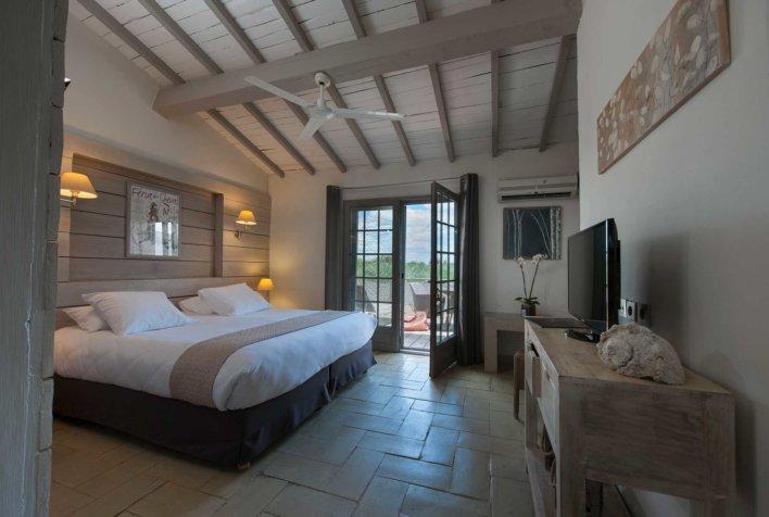 Suite avec lit double, tête de lit en bois et linge de lit en patchwork de tissus