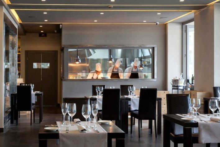 Salle de restaurant avec cuisine ouverte derrière une verrière