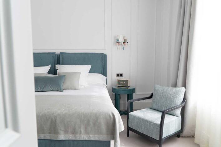 Chambre avec lit et fauteuil aux couleurs bleutées