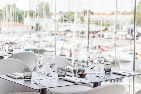 Table dressée avec vue sur un port de pêcheurs