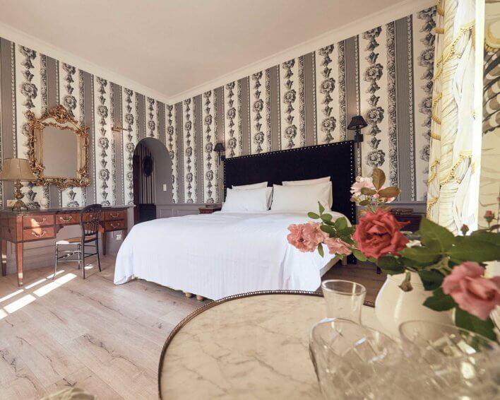 Chambre double avec lit en linge blanc, tapis au papier peint à motif, mobilier en bois anciens
