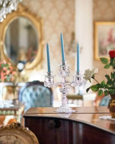 Photo de détail sur le plateau d'un piano à queue, bougeoir et bougies bleu, quelques éléments de décor en arrière plan