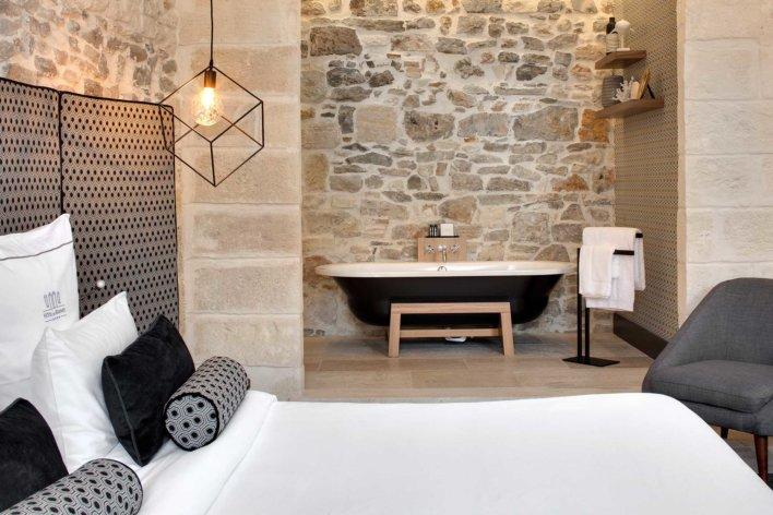 Chambre avec détails de décoration comme un lustre design et une baignoire en suspension