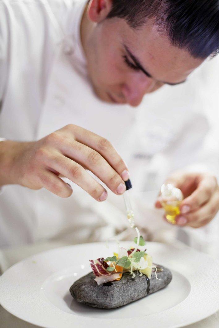 Un chef dépose une gouttte d'huile à l'aide d'une pipette sur un plat