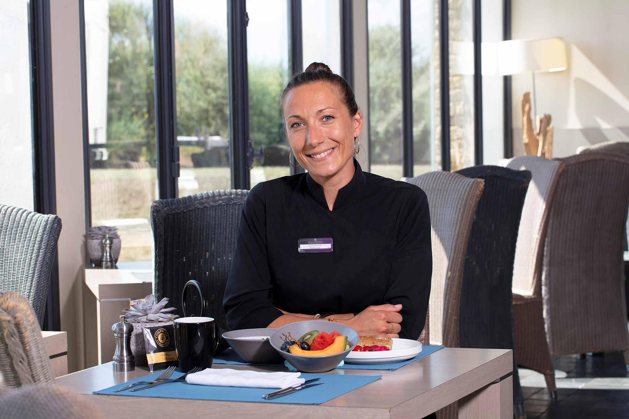 Portrait d'une femme en blouse noir dans une table avec quelques fruits