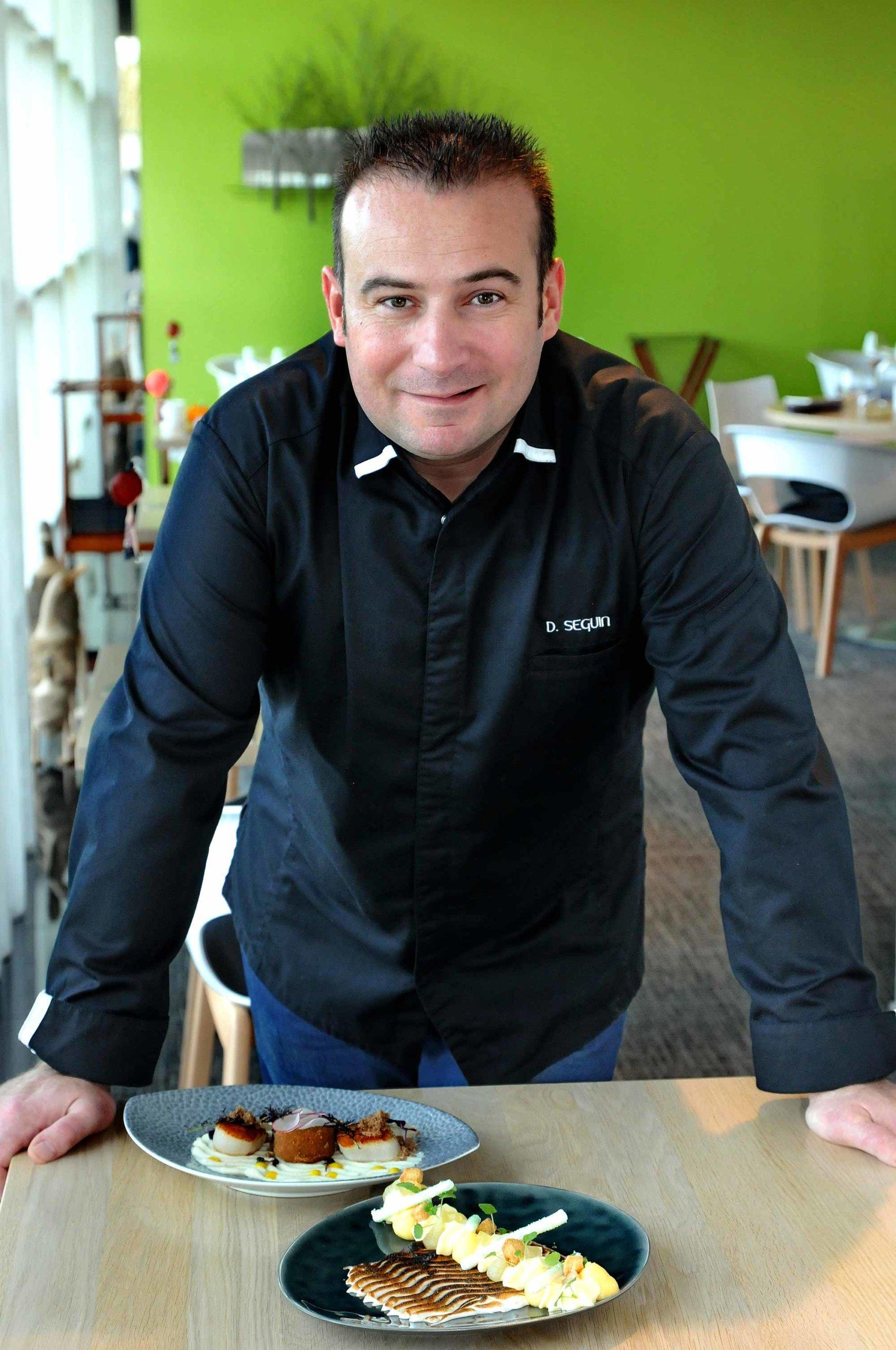 Chef en veste de cuisine noir, dans sa salle de restaurant, debout devant deux plats