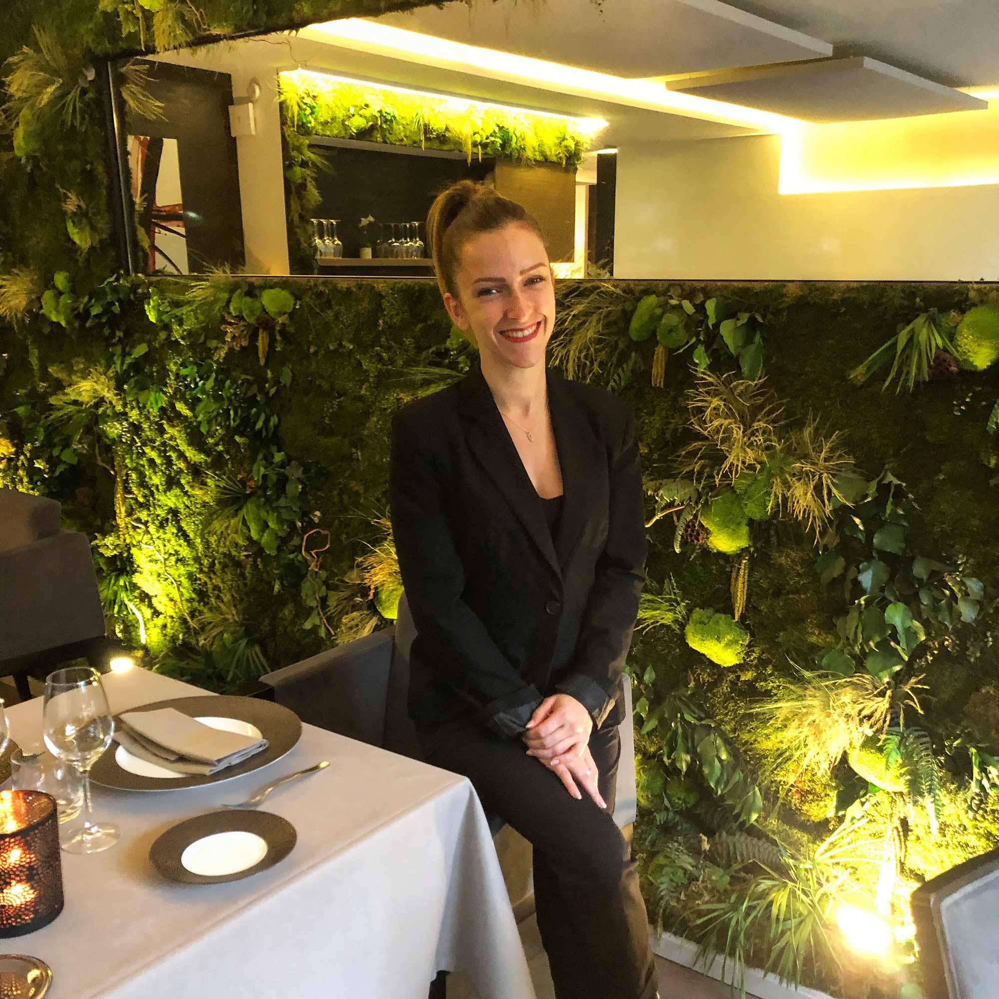 Femme vêtue de noir, dans une salle de restaurant avec un mur végétal en arrière-plan