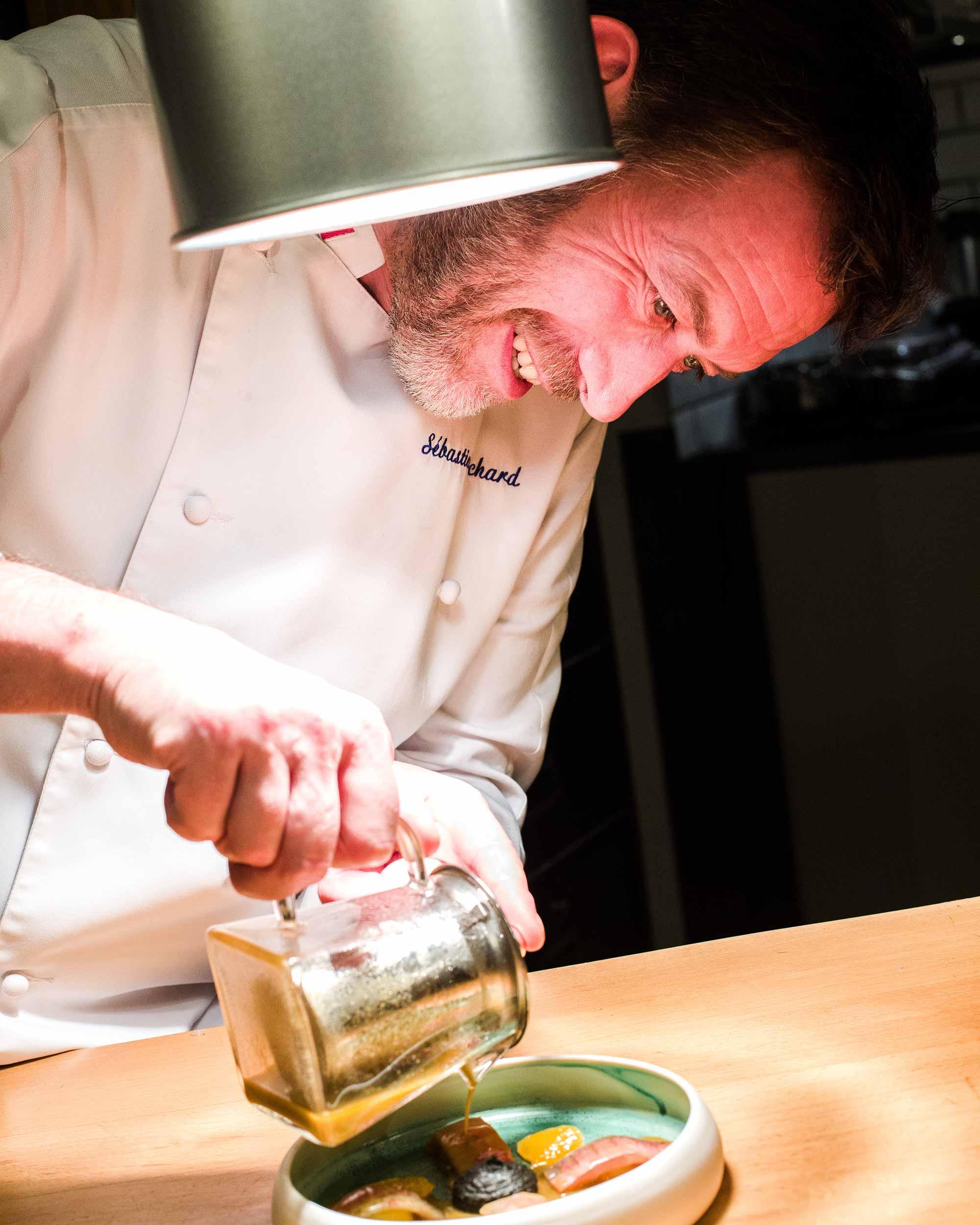 Chef en train de verser un jus vert dans une assiette