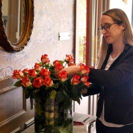 Femme en blazer bleu marin, elle arrange un bouquet de rose