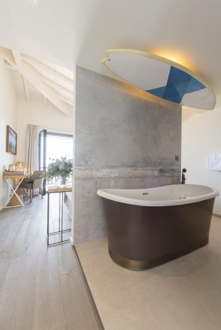 Chambre avec baignoire derrière un paravent en fer forgé