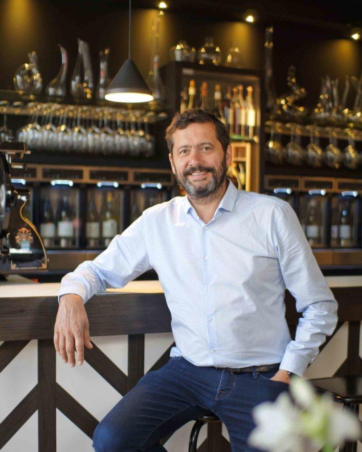 Photo portrait d'un homme sur un tabouret, devant un bar à vin