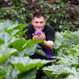 Photo portrait d'un chef, dans un potager, il tient un artichaud en fleur dans la main