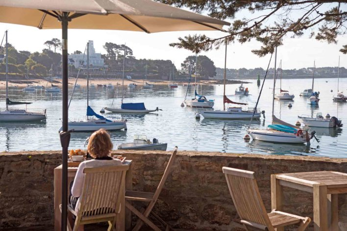 femme sur une chaise de jardin, terrasse face à la mer