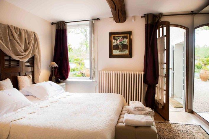 Chambre lit double, linge blanc et fenêtre ouverte