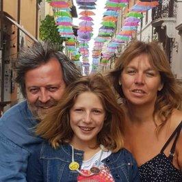 Photo de famille avec un père à gauche, une petit fille au milieu et une mère à droite