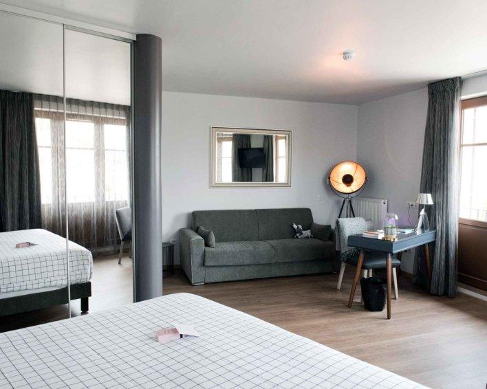 Chambre avec espace canapé et bureau d'appoint