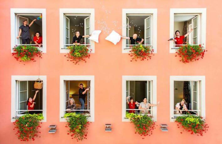 Façade d'un hôtel, couleur orangée avec équipe de chambre à chaque fenêtre