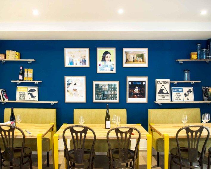 Salle de restaurant avec mobilier jaune et bleu profond au mur