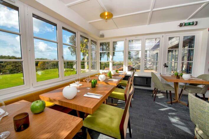 Salle de restaurant avec grand verrière donnant sur parc verdoyant