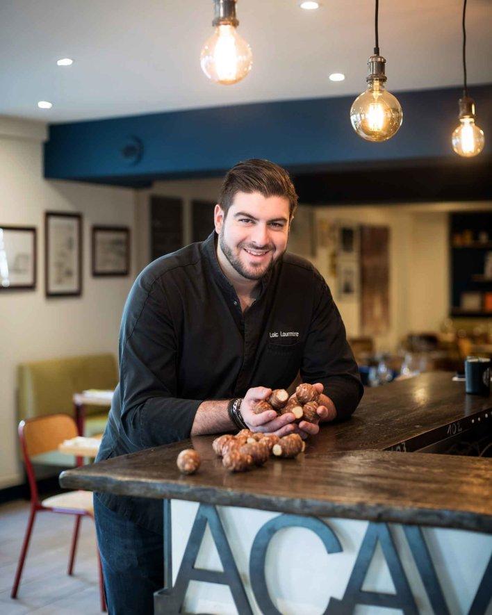 Chef devant un bar en bois tenant des topinambour dans ses mains
