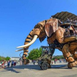 Éléphant en bois mécanique portant des voyageurs sur le dos