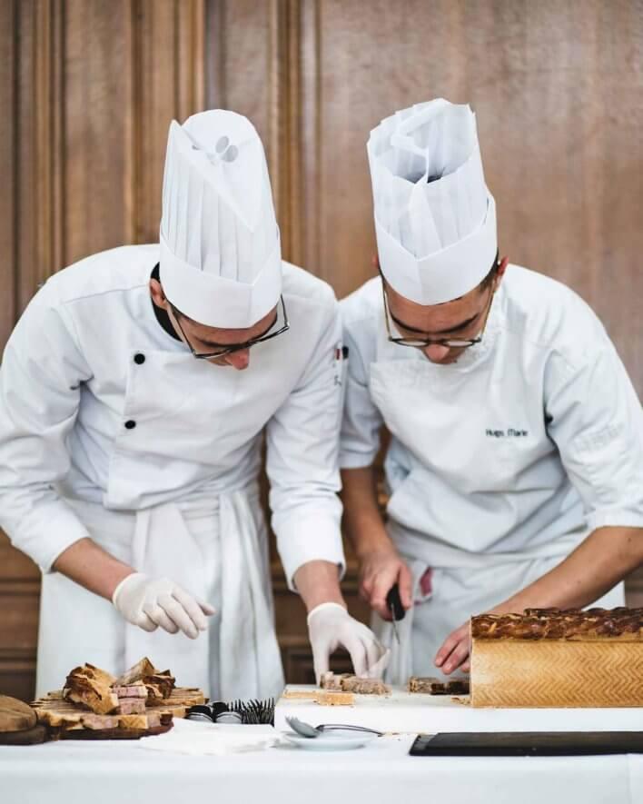 Deux chefs en train de trancher un pâté en croûte