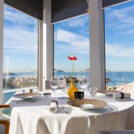 Vue d'une table du restaurant l'Épuisette avec en arrière plan une vue sur le petit port de pêche du Vallon des Auffes