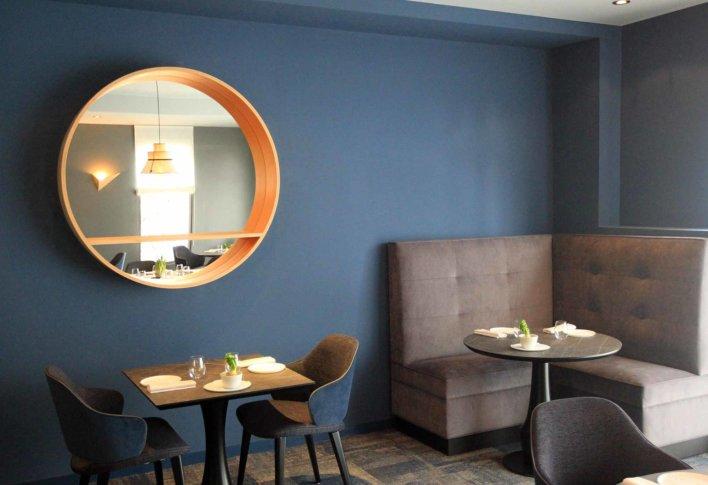 Salle de restaurant avec table, banquette et miroir rond