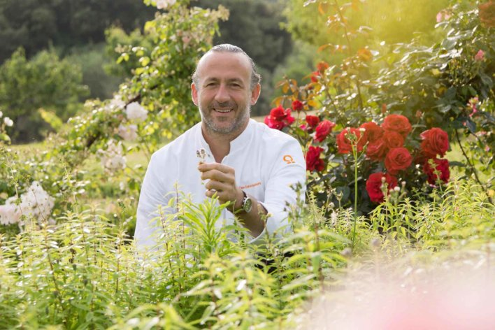 Chef dans un potager avec une fleur à la main