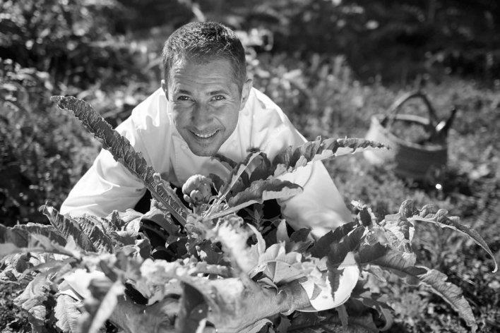 Photo en noir et blanc d'un chef dans un potager tenant un artichaut