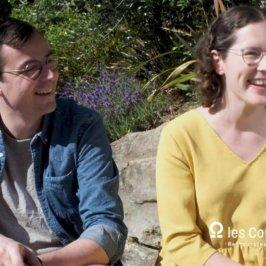 Une femme à droite en robe jaune et un homme à gauche en chemise bleue