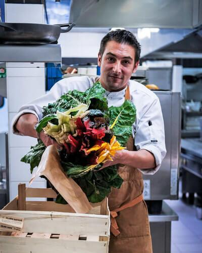 un chef en cuisine sort des légumes d'une cagette en bois