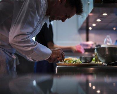 Un chef en cuisine dresse un plat