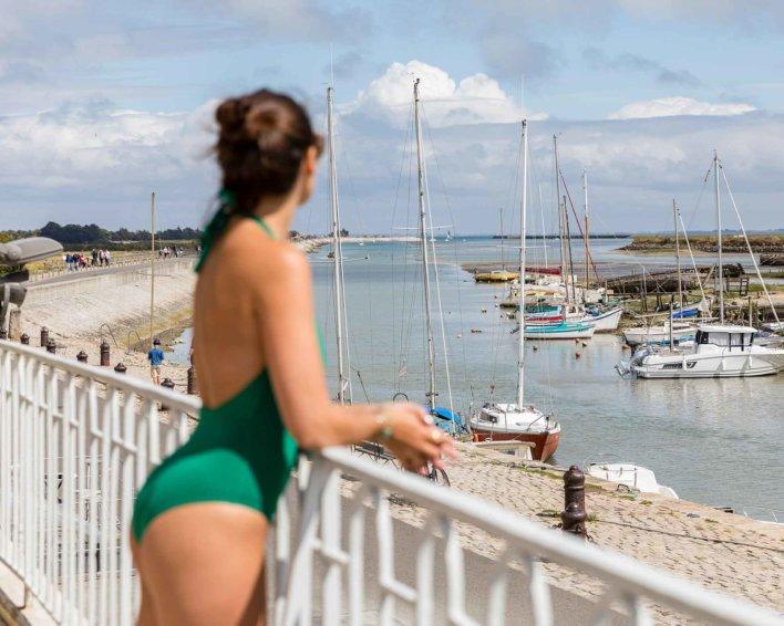 Femme en maillot vert devant une petite plage