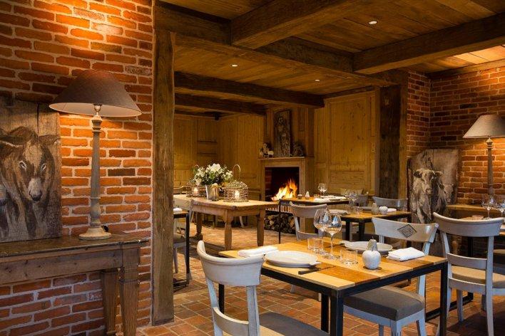 Salle de restaurant avec cheminée et poutres apparentes