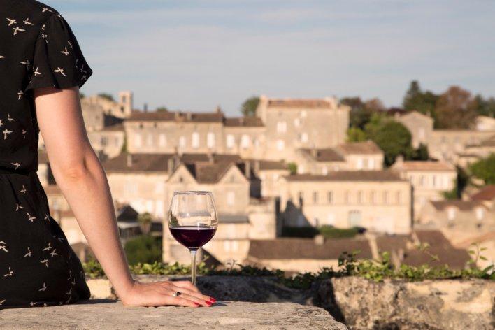 Femme avec un verre de vin au village de Saint Emilion © Favoreat