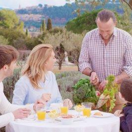 Famille composée de jeunes parents et d'un garçon en train de prendre leur petit-déjeuner en terrasse tout en discutant avec le chef en train de leur présenter des produits frais du jardin