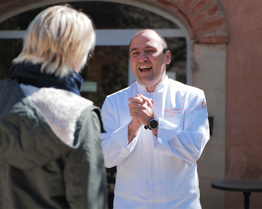 Un chef en veste blanche parle à une voyageusede dos