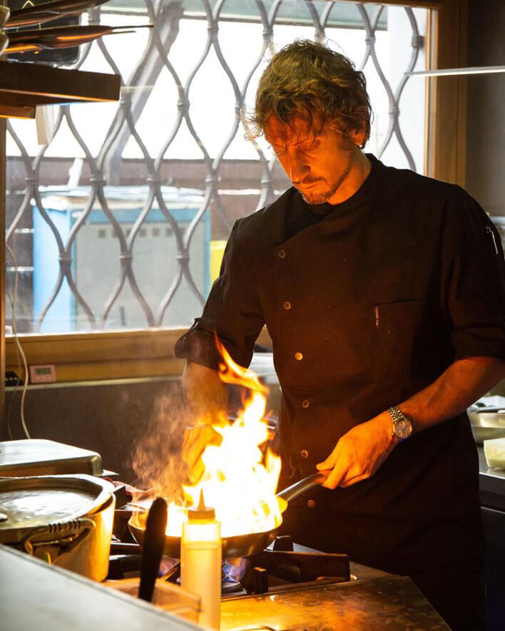 Chef en cuisine flambe une poêle