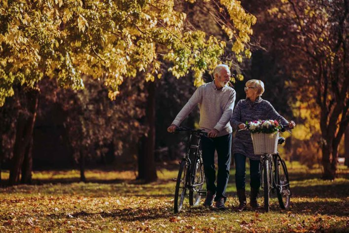 Une femme et un homme marchent l'un à côté de l'autre, automne à vélo